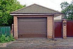 在一个私有车库的布朗门和有一个邮箱的铁门在路附近 库存照片