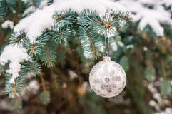 在一个积雪的树枝的银色圣诞节球 库存图片