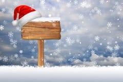 在一个积雪的空白的标志的圣诞节帽子 图库摄影