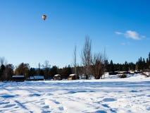 在一个积雪的领域上的五颜六色的热空气气球飞行 免版税图库摄影