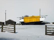 在一个积雪的领域的一条大小船在农场 免版税库存图片