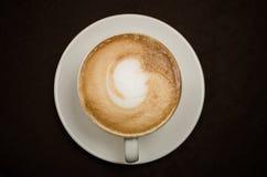 在一个空白杯子的热奶咖啡 免版税库存照片