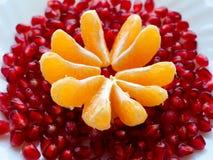在一个空白牌照的新鲜水果 切片普通话和石榴五谷 免版税库存照片