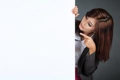 在一个空白的横幅、点和厕所后的亚洲女实业家立场 库存图片
