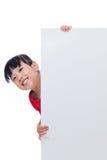 在一个空白的白板后的亚裔中国小女孩 库存图片