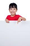 在一个空白的白板后的亚裔中国小女孩 库存照片