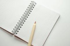 在一个空白的笔记薄的背景的木棕色铅笔 免版税库存照片