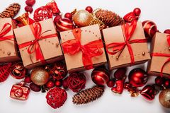 在一个空白背景的圣诞节装饰和礼品 红色锥体、球和用红色丝带装饰的金米黄礼物 图库摄影