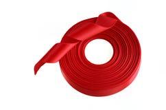 在一个空白背景的红色丝带卷 免版税图库摄影