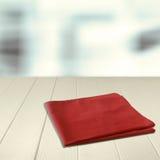 在一个空的木柜台的红色餐巾 免版税库存图片