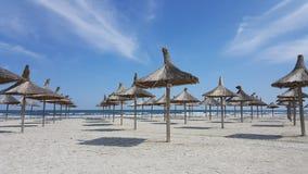在一个空的海滩的伞 库存照片
