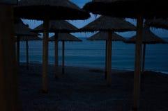 在一个空的海滩的沙滩伞在黄昏 免版税库存图片