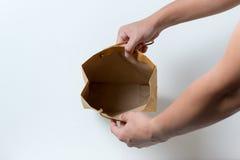 在一个空的纸袋的手上 免版税库存图片
