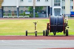 在一个空的绿色足球场的流动喷水隆头 有一个水管的大鼓浇灌的橄榄球场 免版税库存照片