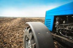 在一个空的领域的老蓝色拖拉机特写镜头 农机,野外工作 免版税库存图片