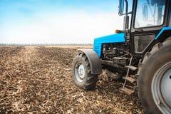 在一个空的领域的老蓝色拖拉机 农机,野外工作 免版税库存图片