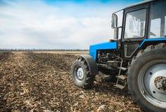 在一个空的领域的老蓝色拖拉机 农机,野外工作 图库摄影
