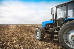 在一个空的领域的老蓝色拖拉机 农机,野外工作 免版税库存照片