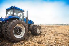 在一个空的领域的背景的蓝色拖拉机 免版税库存照片