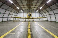 在一个空的飞机棚里面的葡萄酒老黄色战争飞机 免版税图库摄影