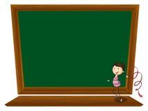 在一个空的黑板前面的女孩跳舞 免版税库存图片