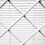 在一个窗口前面的白合金栅格与一个白色窗帘 库存照片
