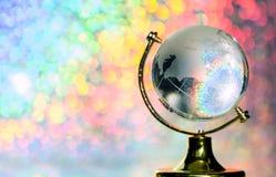 在一个立场的玻璃地球在与光芒的彩虹背景 行星与大陆小雕象的地球地球在桌上 免版税图库摄影