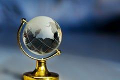 在一个立场的玻璃地球在与光芒的蓝色背景 行星与大陆小雕象的地球地球在桌上 库存照片