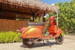 在一个竹大厦前面停放的一辆老意大利滑行车 从意大利的橙色经典脚踏车大黄蜂类 背景竹子 库存照片