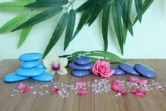 在一个竹木板的禅宗生活时尚堆积的装饰小卵石有一朵桃红色花和一朵兰花的在绿色和叶子 免版税库存照片
