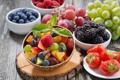 在一个竹碗和新鲜的莓果的水果沙拉 免版税库存图片