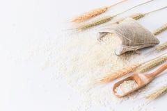 在一个竹篮子的未加工的米与在白色背景和麦子隔绝的米匙子 库存照片