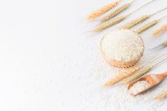 在一个竹篮子的未加工的米与在白色背景和麦子隔绝的米匙子 免版税库存照片