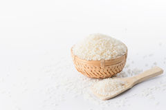 在一个竹篮子的未加工的米与在白色背景隔绝的米匙子 库存图片