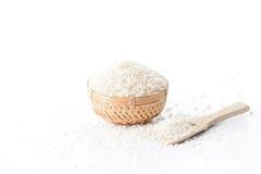 在一个竹篮子的未加工的米与在白色背景隔绝的米匙子 免版税库存照片