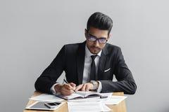 在一个笔记本的商人文字在一个咖啡馆、片剂、电话和文件的灰色背景在桌上 库存照片