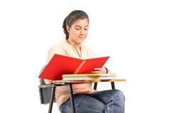 在一个笔记本的女孩文字在学校书桌上 免版税库存图片