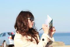 在一个笔记本的女孩文字,在汽车背景  库存照片