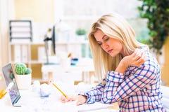在一个笔记本的妇女文字在办公室 图库摄影