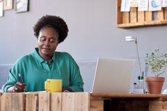 在一个笔记本的非洲企业家文字在她的办公桌 库存照片