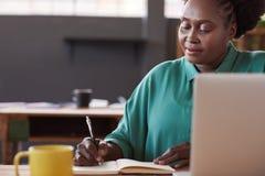 在一个笔记本的非洲女实业家文字在她的书桌 免版税图库摄影