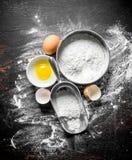 在一个筛子和一个瓢的面粉用鸡蛋 图库摄影