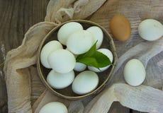 在一个筛子的鸡蛋在一张木桌上 库存图片