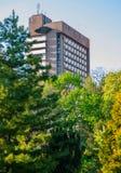 在一个简单的样式的高层旅馆大厦在绿色树背景  免版税库存图片