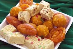 在一个简单的白色盘的五颜六色的印地安人屠妖节甜点 免版税图库摄影