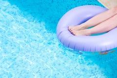 在一个管或可膨胀的圆环的女性腿在水池 使布赖顿椅子日甲板英国节假日懒人海边有风夏天的星期日靠岸 库存图片