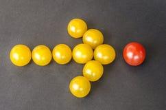 在一个箭头的形状的黄色西红柿在黑暗的背景的 图库摄影