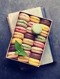在一个箱子的五颜六色的蛋白杏仁饼干在书 免版税库存照片