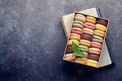 在一个箱子的五颜六色的蛋白杏仁饼干在书 库存照片