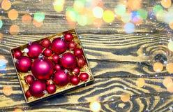 在一个箱子的圣诞节球在与bokeh和雪作用的木背景 库存照片